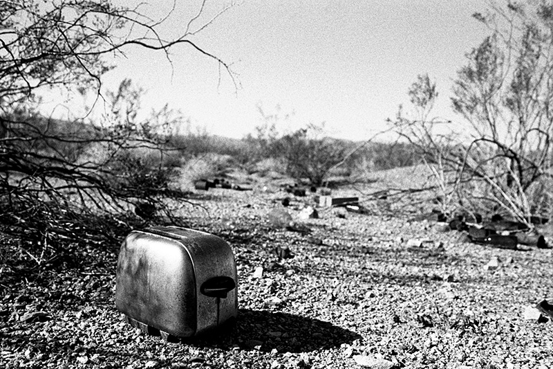 toaster on floor of desert with bottle scattered behind