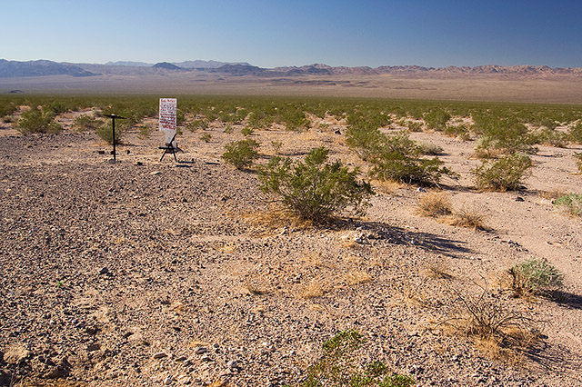 image of desert with sign, chair, and lecturn in the distance