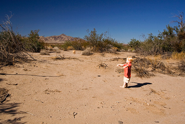 toddler throwing a wax skull in the middle of the desert