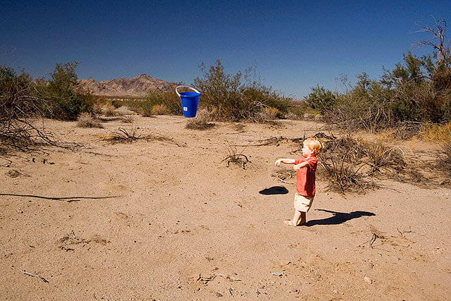 toddler throwing a bucket in the middle of the desert