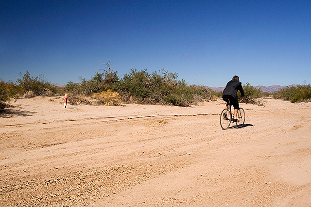 cyclist riding by toddler in the middle of nowhere